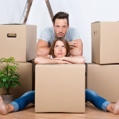 21162053 - tired couple sitting between many boxes in their new home